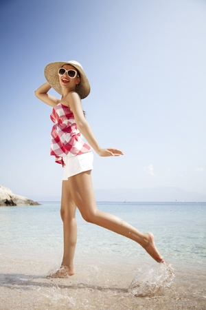 young female in retro outfit, jumping around on the beach