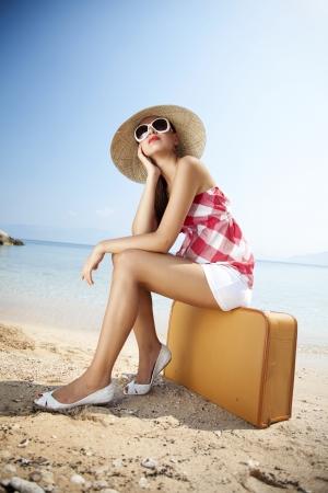 suitcases: jonge femaled vormgegeven in 50s zomer outfit zittend op een retro koffer op het strand