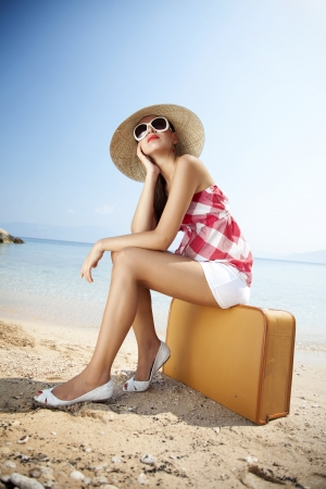 vertical: young femaled styled in 50s summer outfit sitting on a retro suitcase on the beach