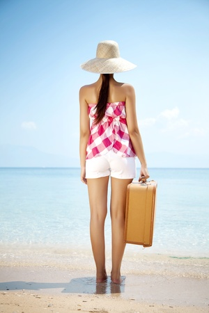 young female standing on the beach with vintage suitcase Stockfoto