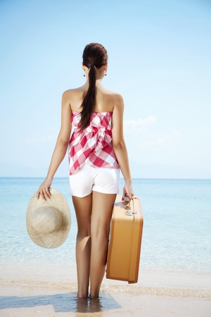 young female standing on the beach with retro suitcase photo