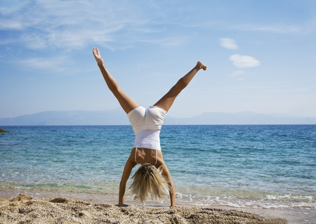 woman doing cartwheel on the beach fit female  photo