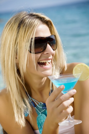 turquise: laughing woman drinking cocktail by the sea Stock Photo