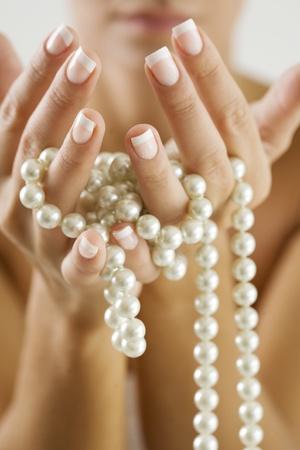 vrouwelijke handen met parels Stockfoto