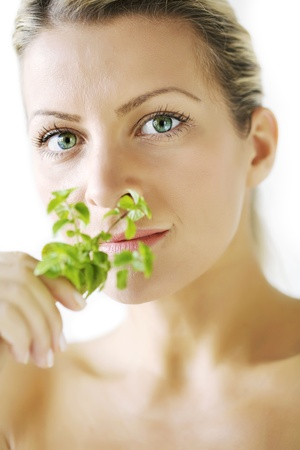 herbal remedy: female smelling mint branch, focus is on the eyes, not on the plant Stock Photo