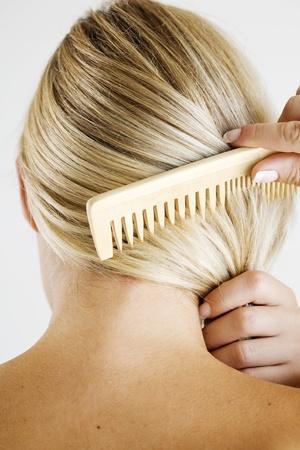 combing hair: woman combing hair Stock Photo