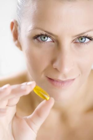 gelatine: woman holding gelatine capsule, focus is on the eyes Stock Photo