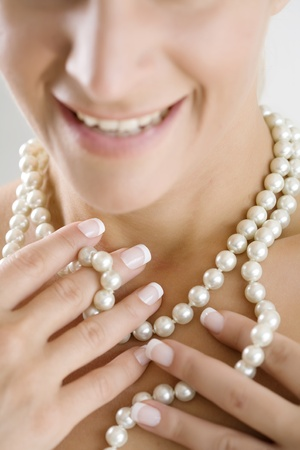 woman playing with her pearl necklace