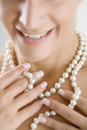 perlas: mujer jugando con su collar de perlas Foto de archivo