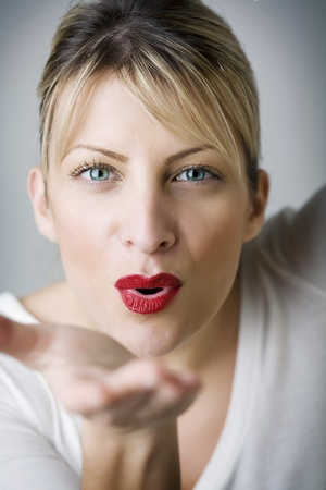 beautiful woman blowing a kiss, skin has been retouched to keep texture
