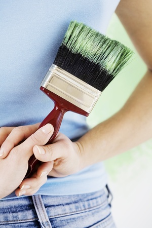 woman holding pait-brush behind her back whilst admiring her work Stock Photo - 10780592