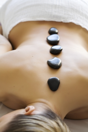 massage stones: female with hot stones on the back