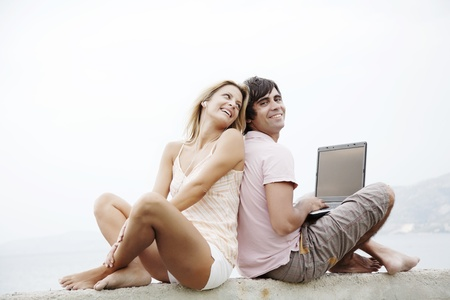 laptop outside: young couple sitting on a wall each with their own piece of technology Stock Photo