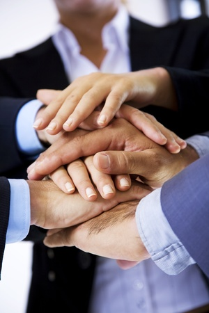 partnership power: business people putting their hands on top of each other