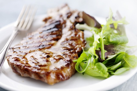 juicy grilled pork chop  neck cut  with greens photo