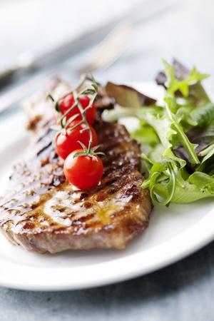 juicy grilled pork fillet steak with greens and cherry tomatos Standard-Bild