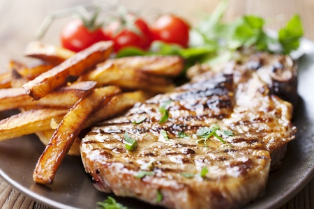 cutlets: juicy grilled pork chop  neck cut  with greens Stock Photo