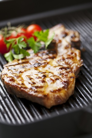 green's: juicy grilled pork chop  neck cut  with greens Stock Photo