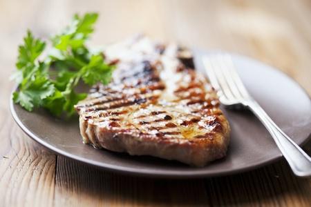 juicy grilled pork chop  neck cut  with greens Archivio Fotografico
