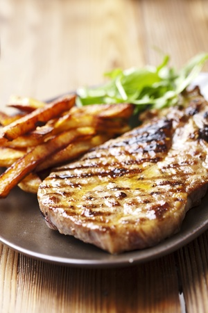juicy grilled pork chop (neck cut) with greens photo