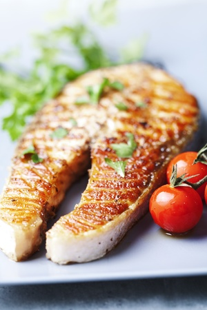 crispy grilled salmon steak with cherry tomatoes and parsley Stockfoto