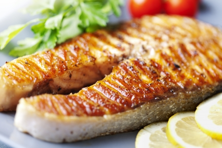 crispy: crispy grilled salmon steak with cherry tomatoes and parsley Stock Photo