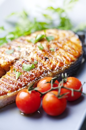 crispy grilled salmon steak with cherry tomatoes and parsley Standard-Bild