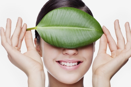 fresh you woman holding leaf in front of eyes
