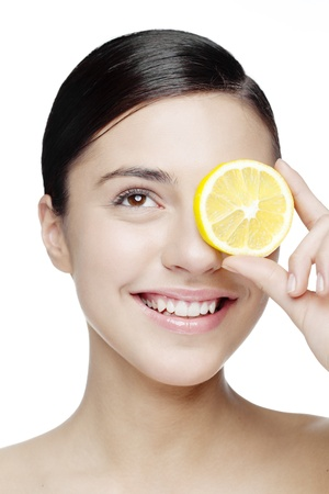 young smiling woman with a lemon slice in front of her eyes Stockfoto