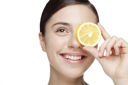 young woman holding lemon slice in front of eye  All skin detail has been kept, no filters used Banque d'images
