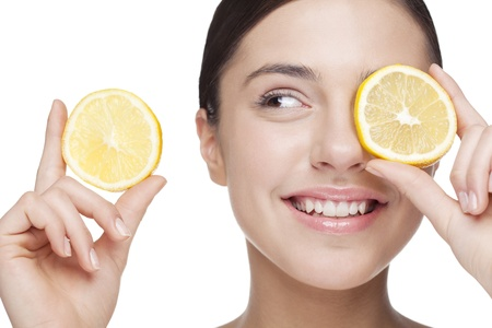 young woman holding lemon slice in front of eye  All skin detail has been kept, no filters used Stock Photo