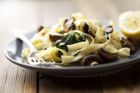 ribbon pasta: vegetarian dish with tagliatelles, spinach and mushrooms Stock Photo