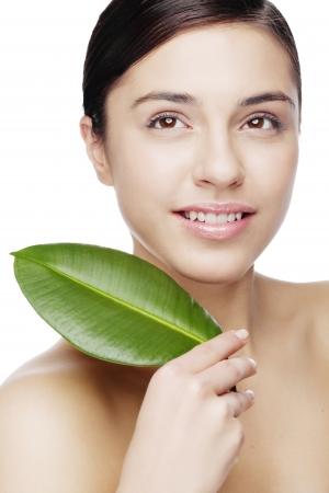 smiling female hiding behind green leaf