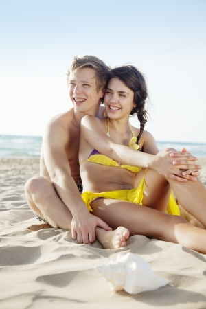couple sitting together on a tropical beach Standard-Bild