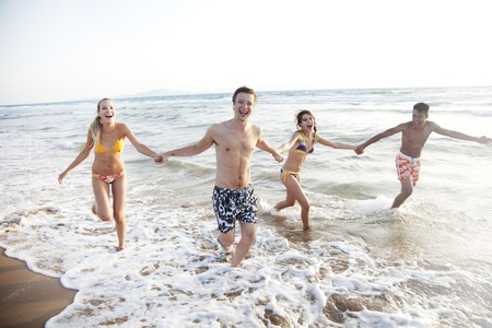 guy on beach: group of young people having fun, running in the surf Stock Photo