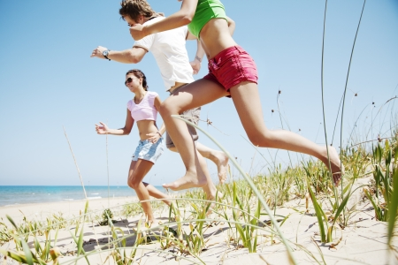 group of happy young people running at the beach