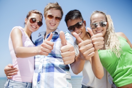 co operation: group of young people doing thumbs up, focus is on the hands in front Stock Photo
