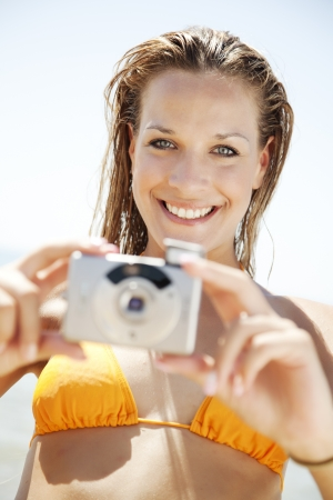 Attractive young woman with digital camera