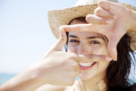 young happy female looking through a frame made from her fingers