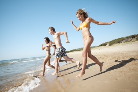 group of young people running into the sea, a little motion blur Stock Photo