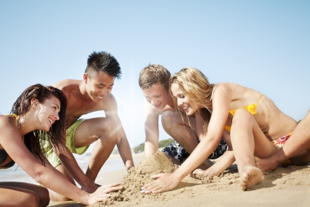 team spirit: group of young people building sand castle in the sand Stock Photo