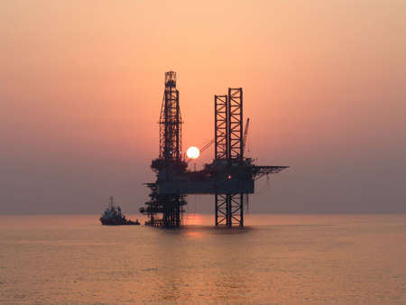 Offshore working boat and oil rig while sunset