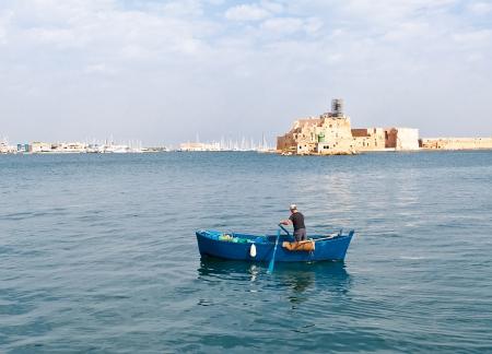 fisherman boat: Fisherman at inner harbor of Brindisi port, Puglia province, Italy Stock Photo