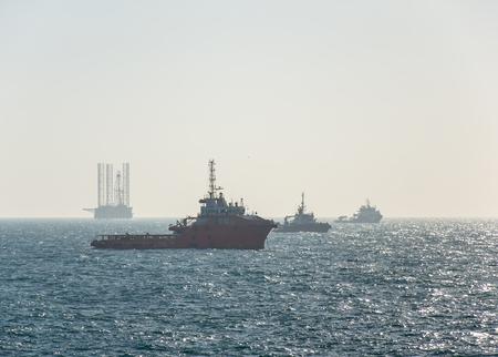 Thre buques en alta mar y plataforma de perforación de espera para la operación de la plataforma movimiento en algún campo petrolero de Arabia Saudita Foto de archivo - 39573114