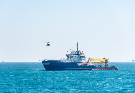 helideck: Helicopter take-off from the helideck of multirole offshore support vessel at some Saudi Arabian oilfield
