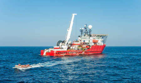 Dynamically positioned diving support vessel lunched inflatable boat with a divers Stock Photo