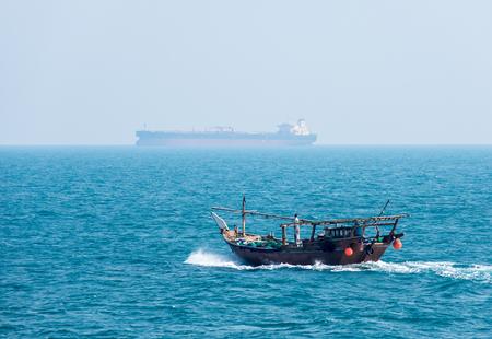 Tradicional barco de madera-dhow a título transversal del buque petrolero Foto de archivo - 39573159