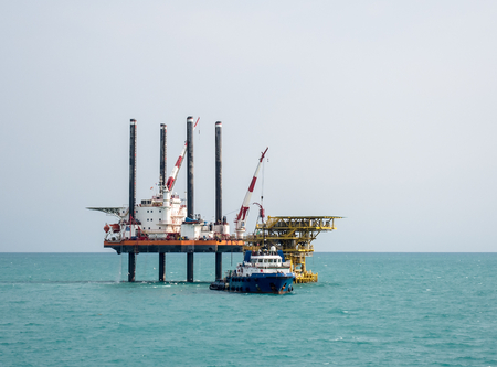 offshore jack up rig: Self-propelled four legs jack-up barge and offshore support vessel around the platform at some Saudi Arabian oilfield