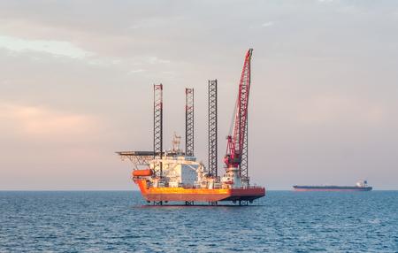 De fondo plano en alta mar barcaza jack-up y un petrolero en el horizonte en algún campo petrolero de Arabia. Foto de archivo - 71982459