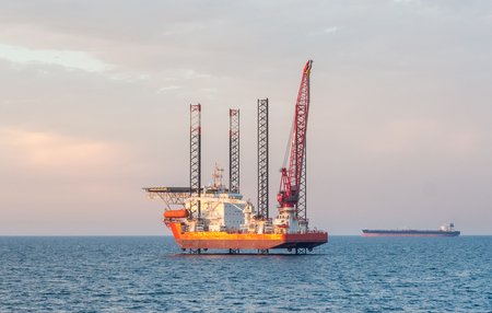 oil and gas: Flat-bottomed offshore jack-up barge and an oil tanker on the horizon at some Arabian oilfield. Stock Photo